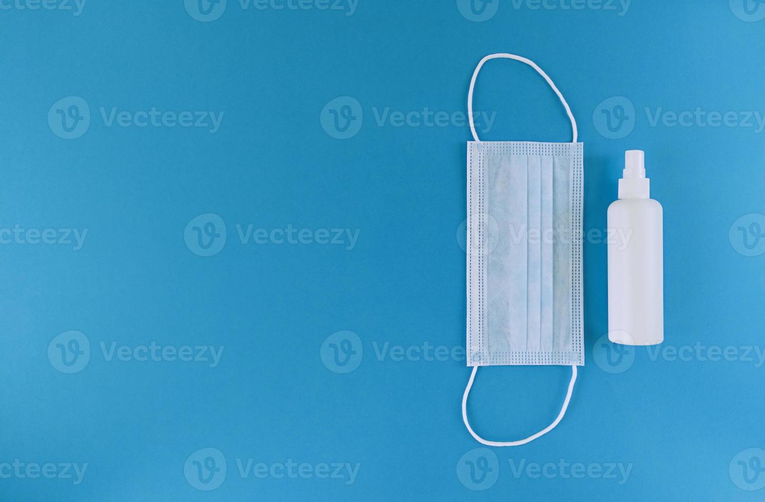 máscara médica branca e desinfetante para as mãos em um frasco com tampa de spray à direita de um fundo azul plano simples leigos com espaço de cópia foto de estoque de conceito médico