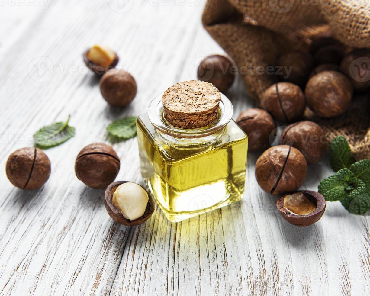 óleo de macadâmia natural e nozes de macadâmia foto