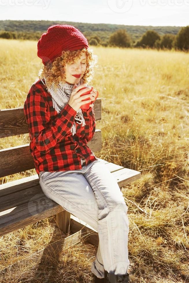 uma jovem mulher com uma camisa xadrez vermelha com um boné de lã e cachecol tomando uma xícara de chá ou café enquanto toma sol, sentada em um banco de madeira em um campo amarelo com luz de fundo do sol de outono foto