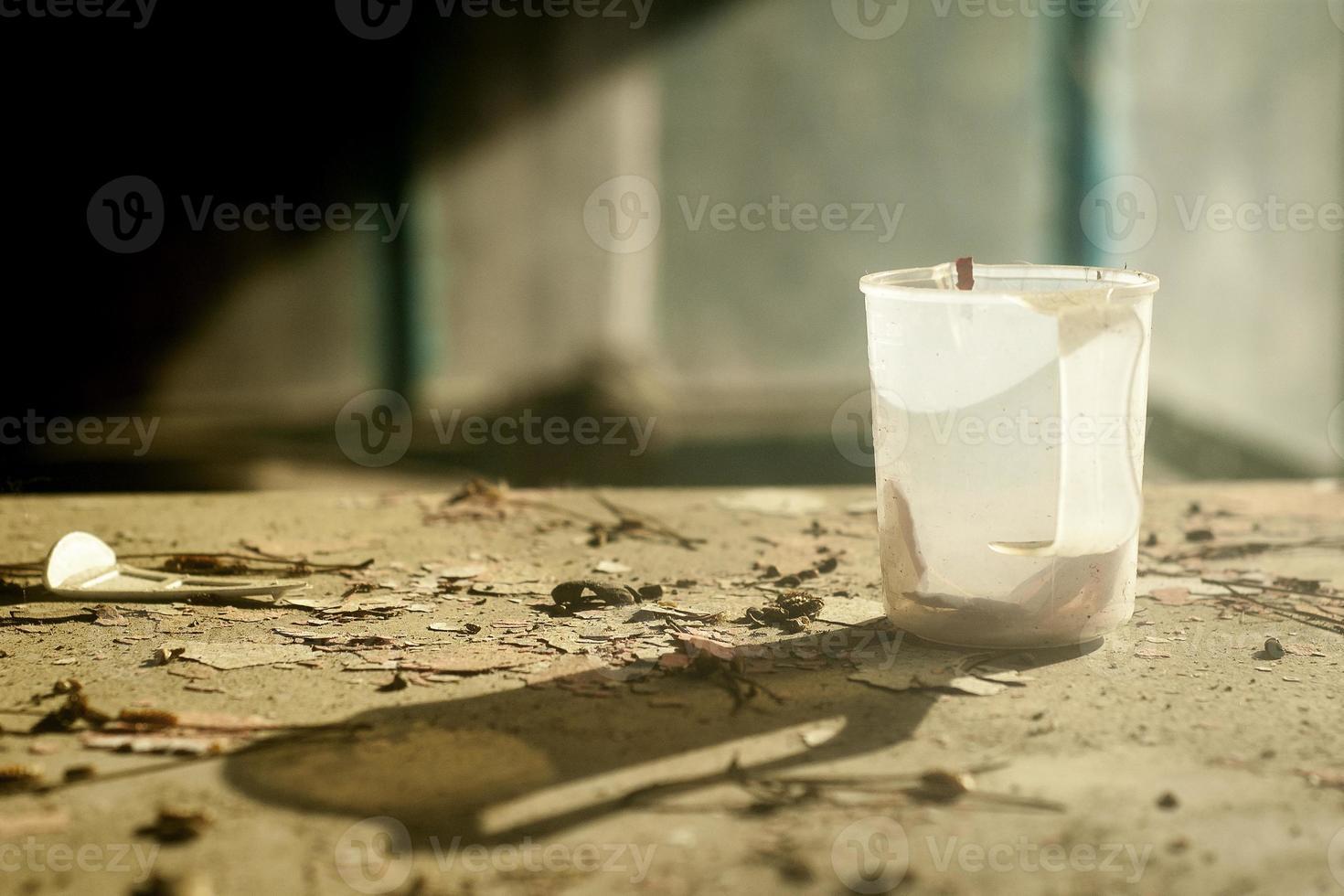 uma imagem de natureza morta com uma velha caneca de plástico em uma mesa devastada foto