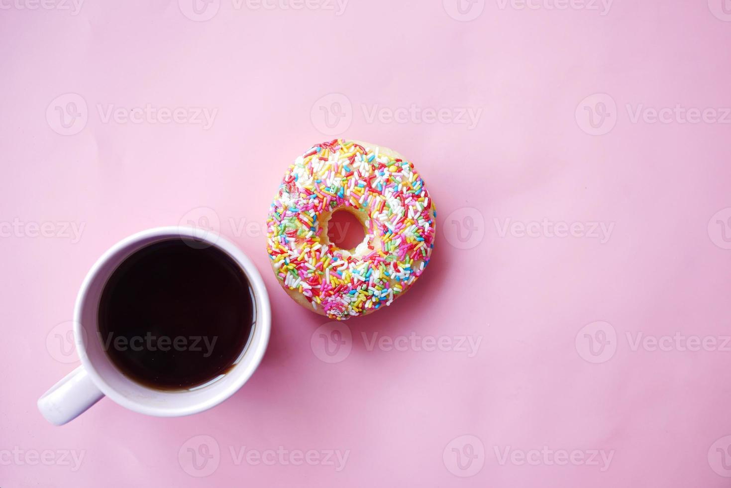 vista superior de rosquinhas saborosas coloridas e xícara de café rosa foto
