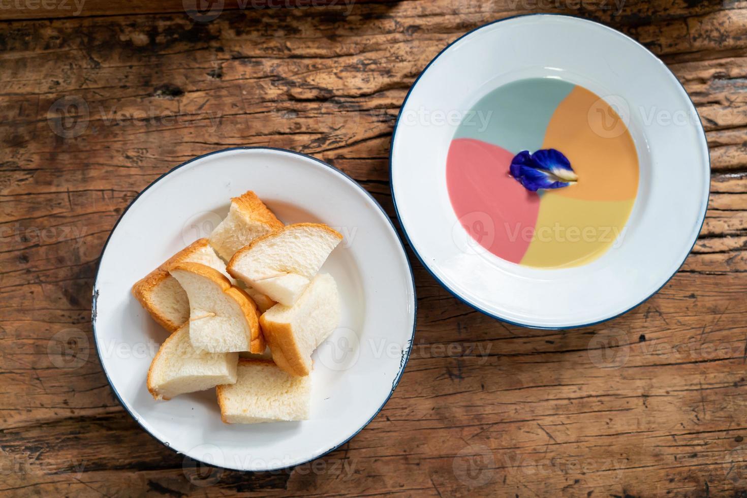 Pão torrado no vapor com creme colorido sobre fundo de madeira foto