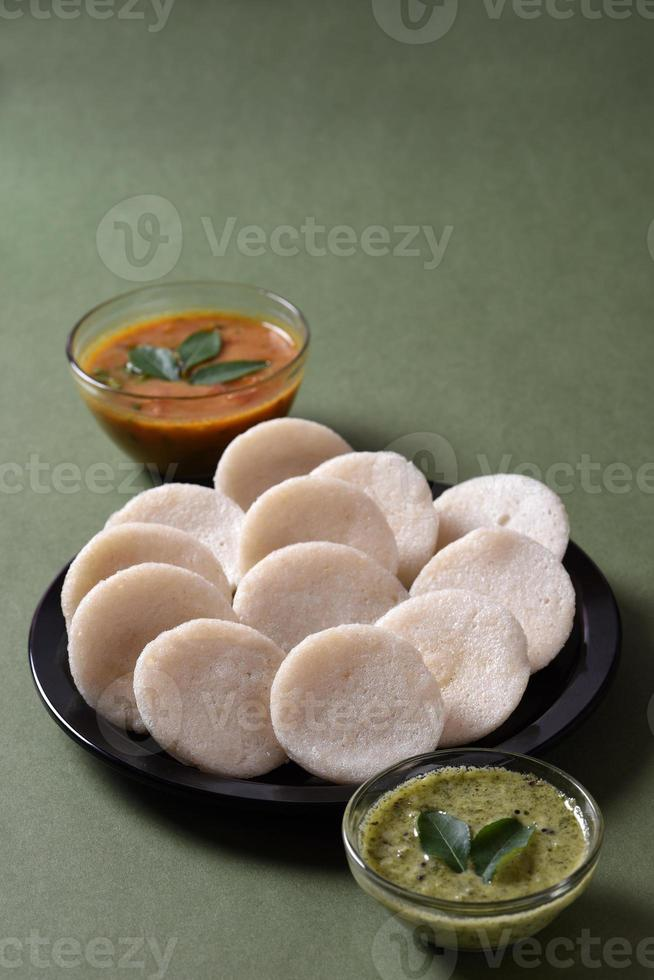 idli com sambar e chutney de coco, prato indiano comida favorita do sul da índia rava idli ou semolina à toa ou rava à toa, servida com sambar e chutney verde. foto