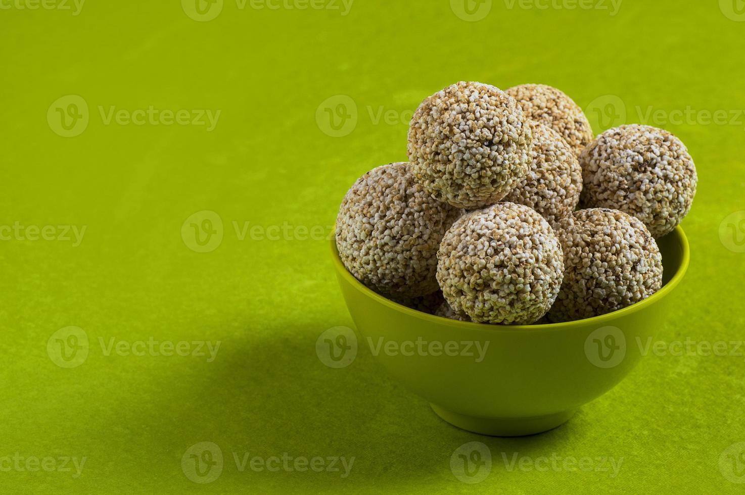 amaranto ou rajgira laddu, cholai ke laddo em tigela verde sobre fundo verde foto