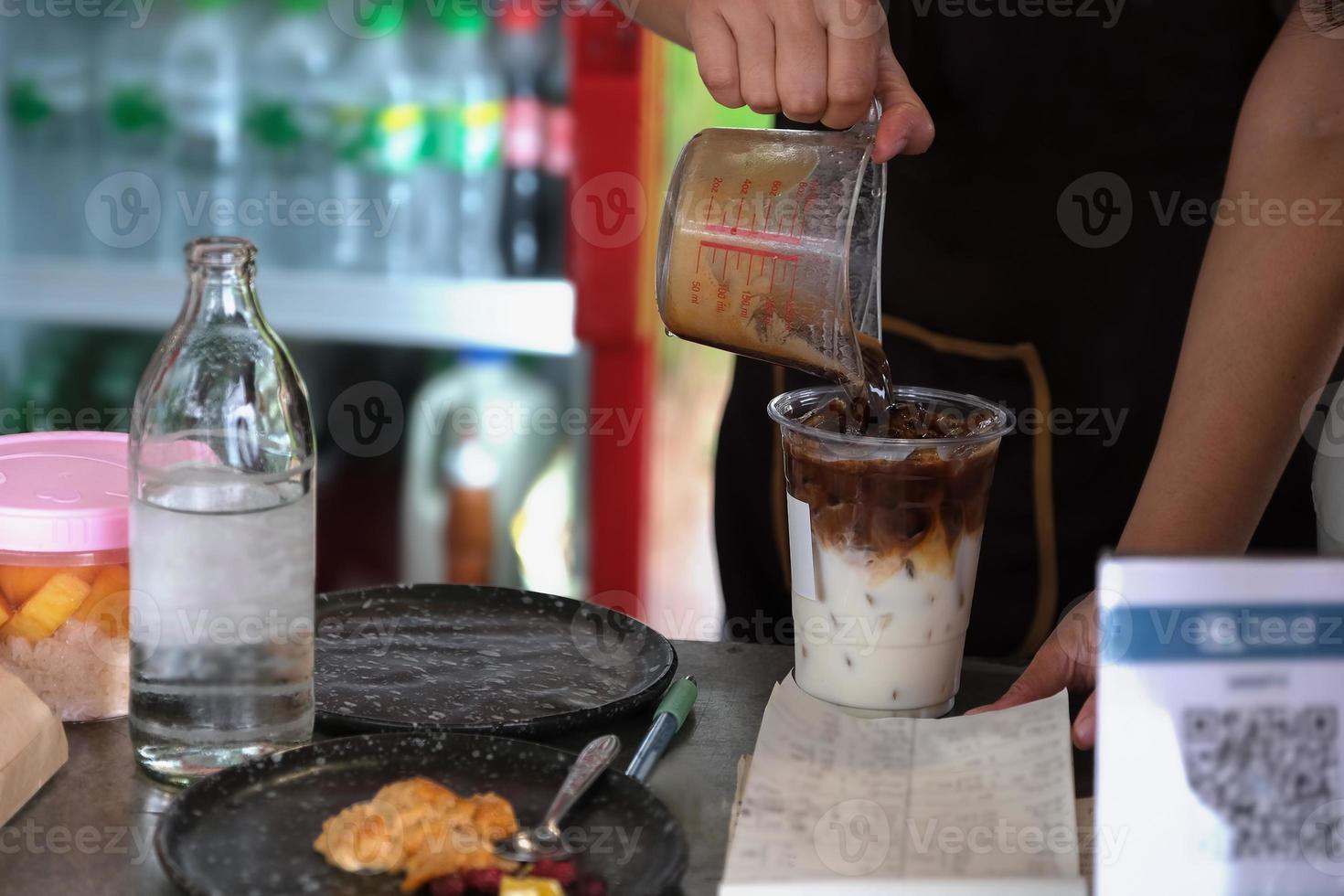 os funcionários estão colocando café em copos para fazer latte para os clientes. foto