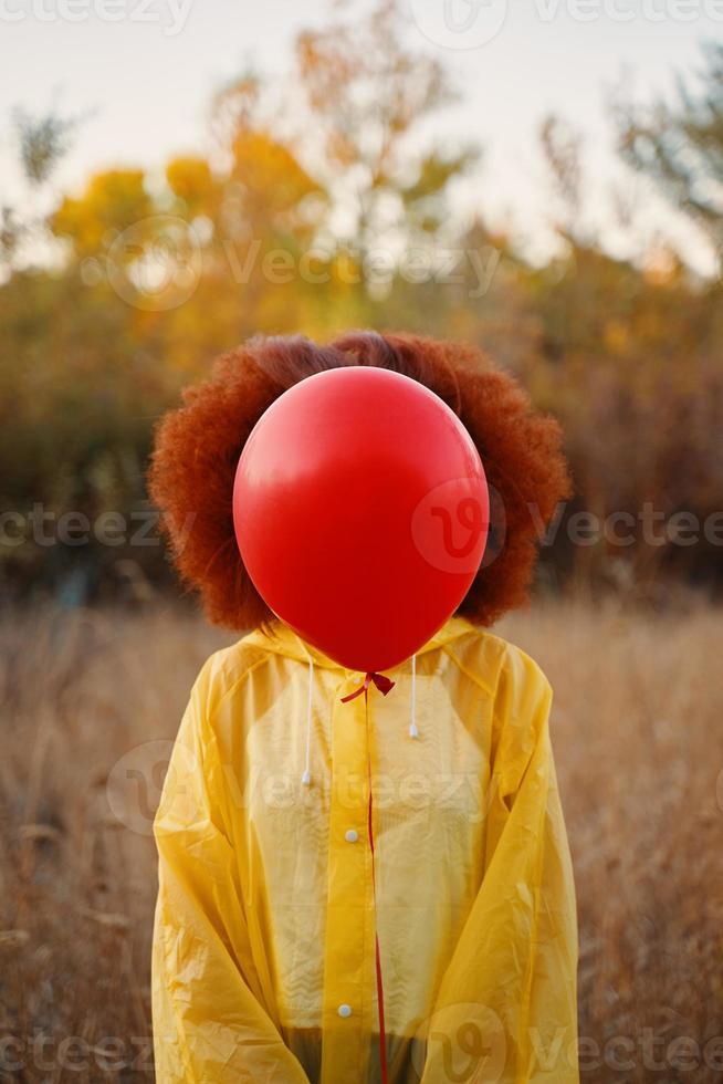mulher com uma capa de chuva amarela segurando um balão vermelho no fundo da floresta. foto