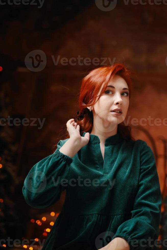 elegante mulher ruiva se senta no colo e ajusta o penteado. foto