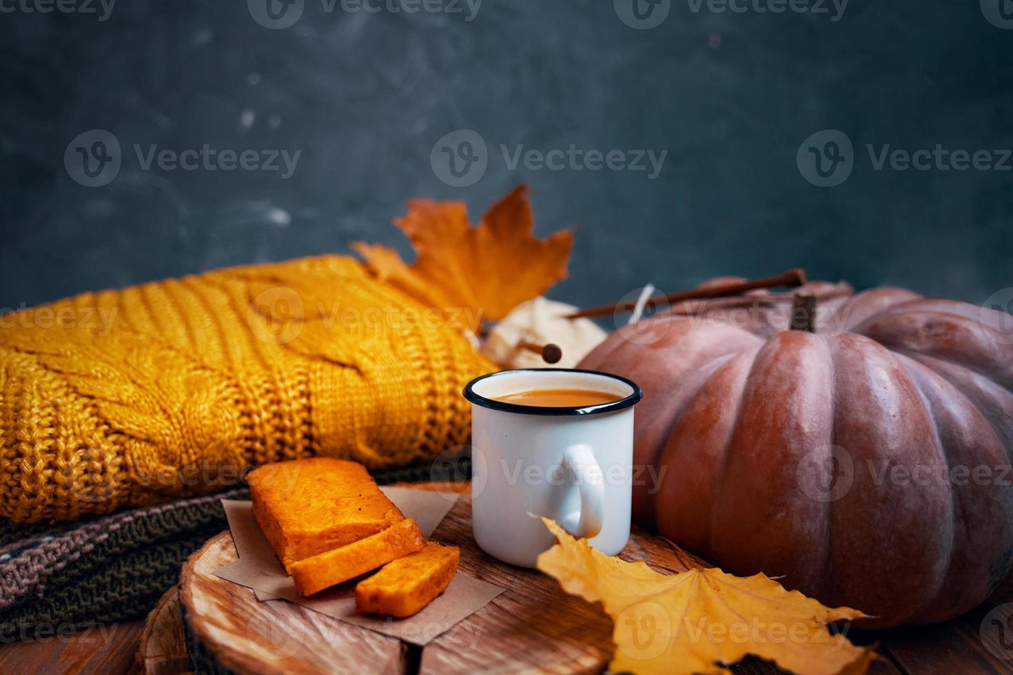 suco, bolo de cenoura no carrinho de madeira, camisola de malha, abóbora e folhas. foto