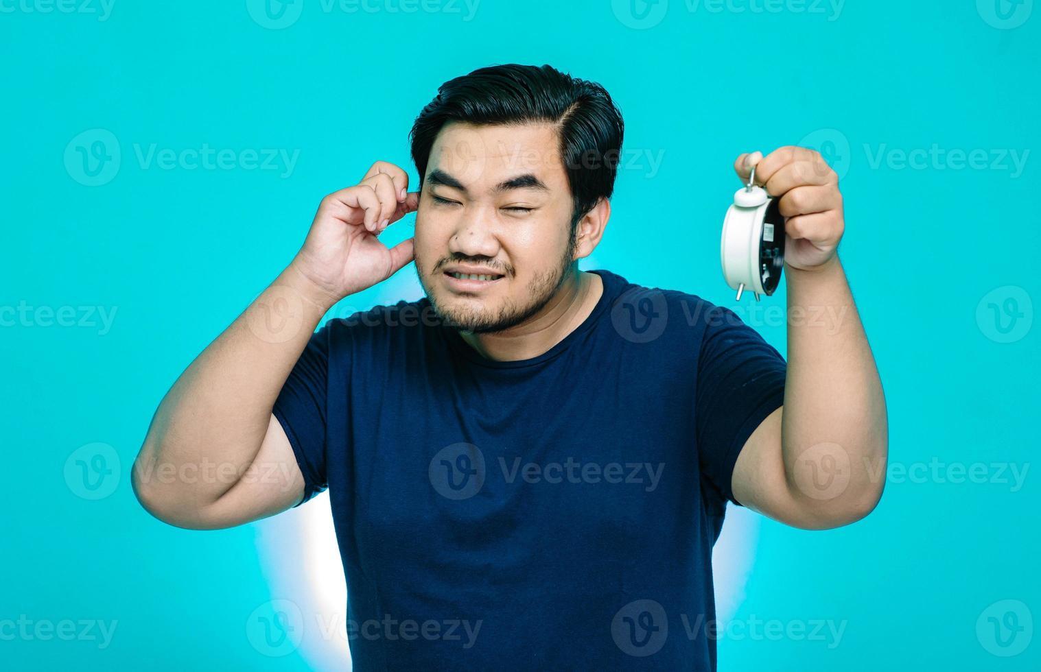retrato de um homem asiático segurando o som de um alarme tocando com as mãos nos ouvidos foto