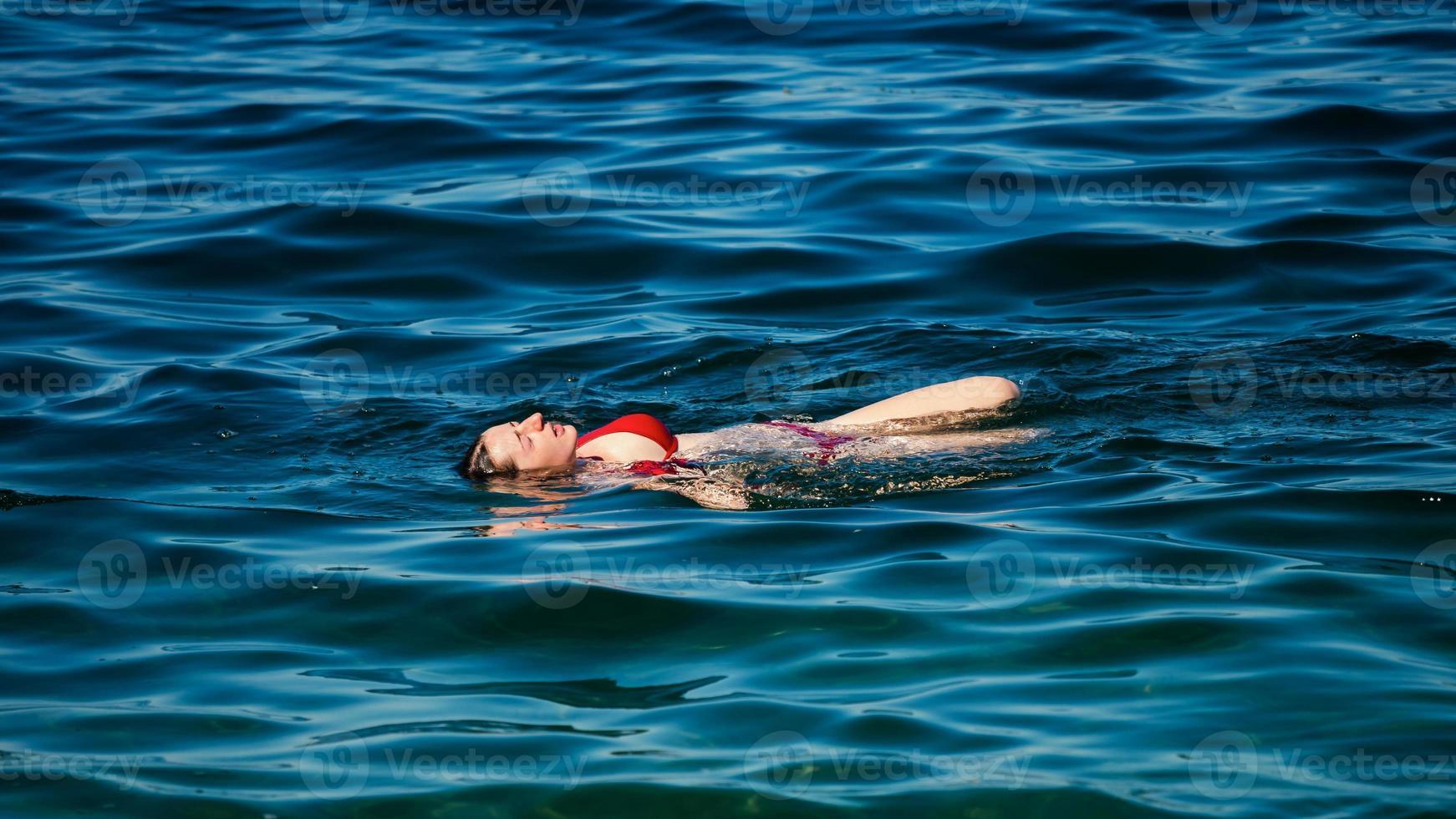 uma jovem nada nas águas cristalinas de um lago de montanha. foto