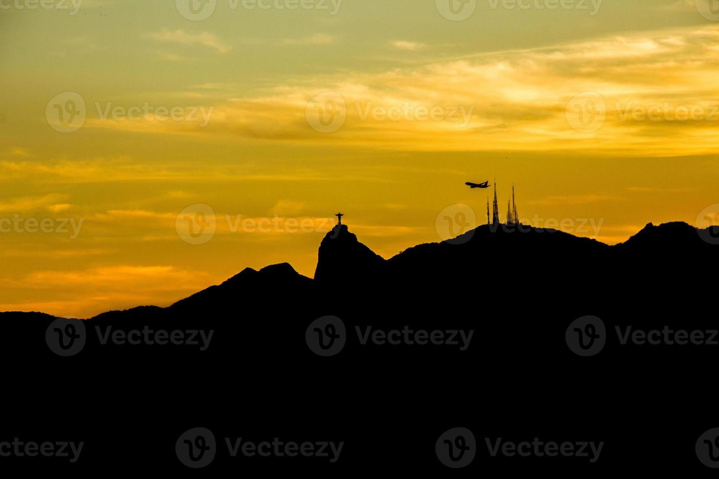 silhueta do cristo redentor com um lindo pôr do sol foto