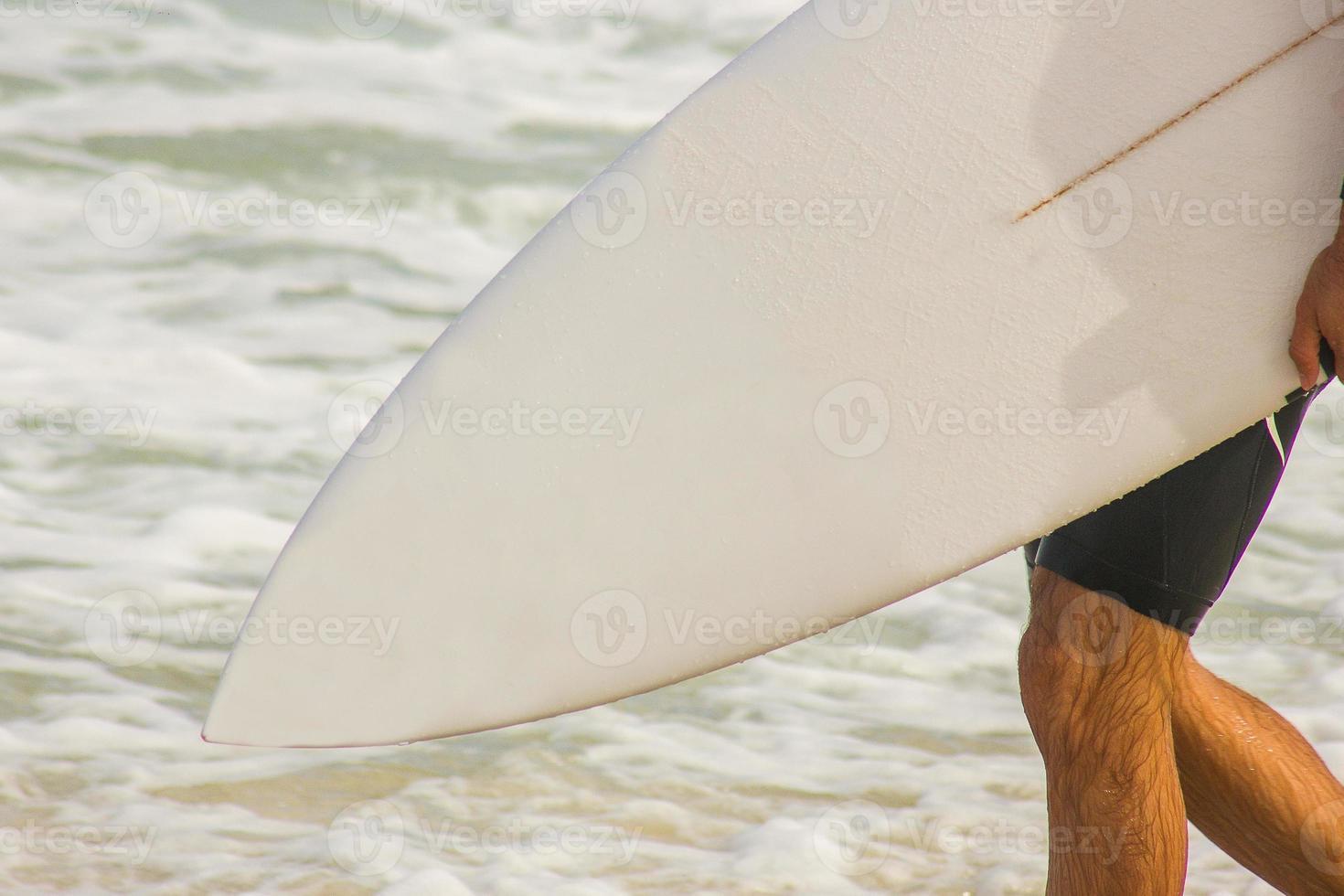 surfista com prancha indo em direção ao mar na praia da barra da tijuca foto