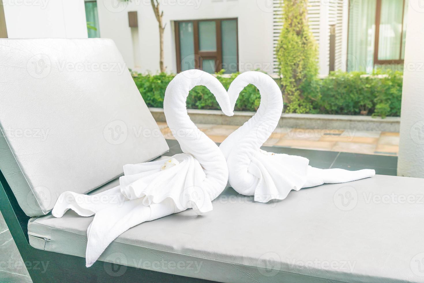 vista de perto de dois lindos cisnes de toalhas na piscina - com efeito sunflare foto