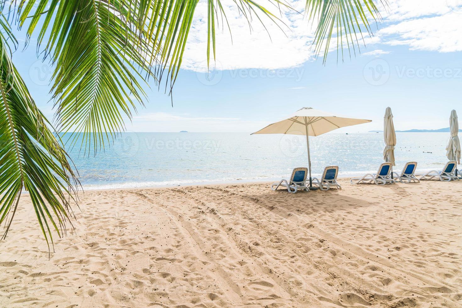 ao ar livre com guarda-sol e cadeira na bela praia tropical e mar foto