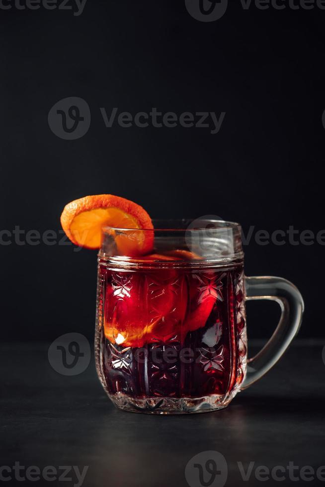 vinho quente quente em copo de vidro com fundo escuro foto