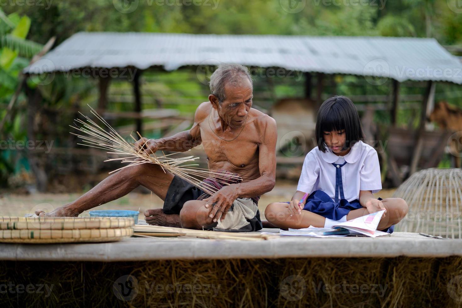 homem idoso e artesanato de bambu com a aluna foto