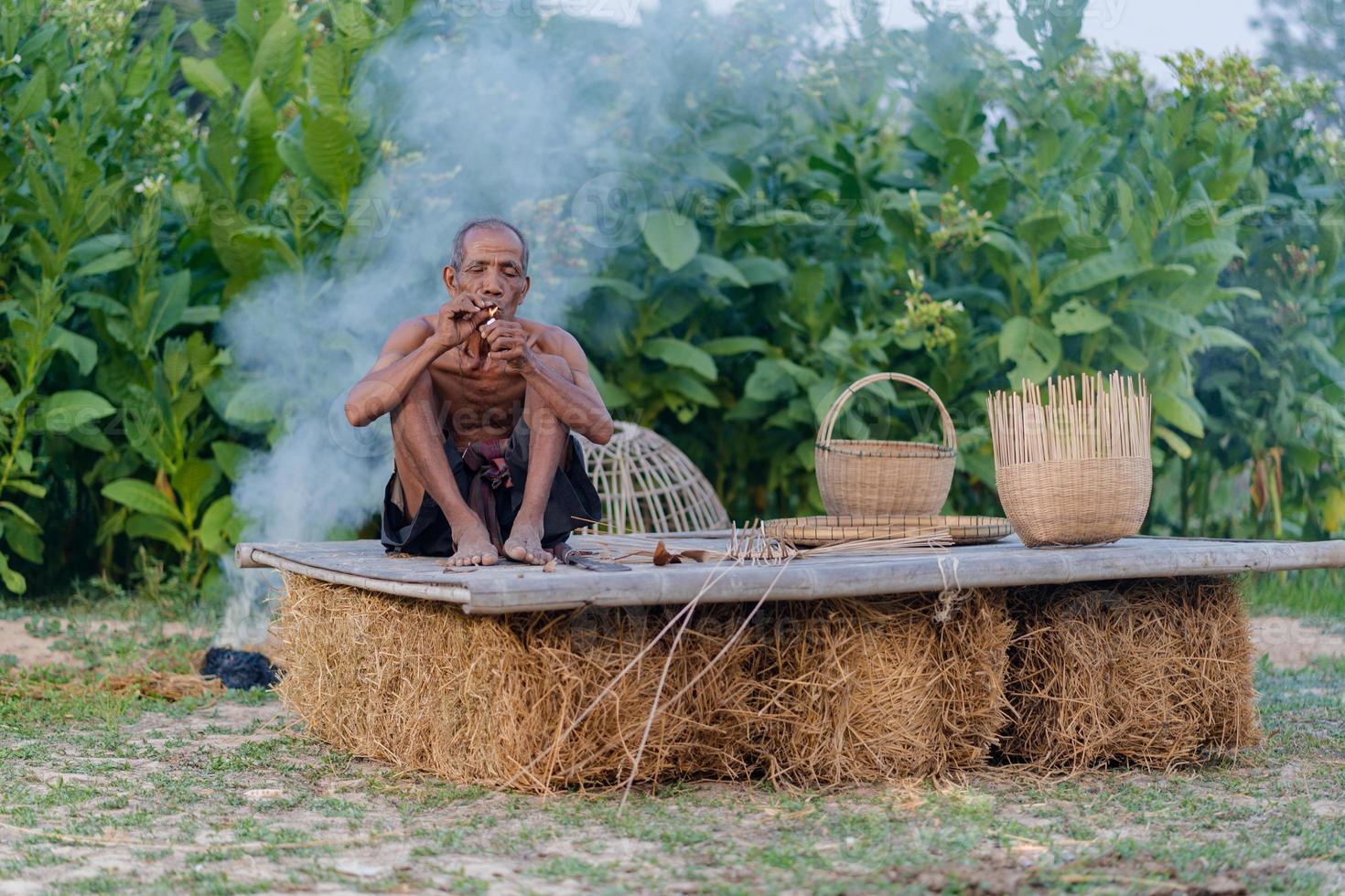 homem idoso com bambu artesanal, estilo de vida dos habitantes locais na Tailândia foto