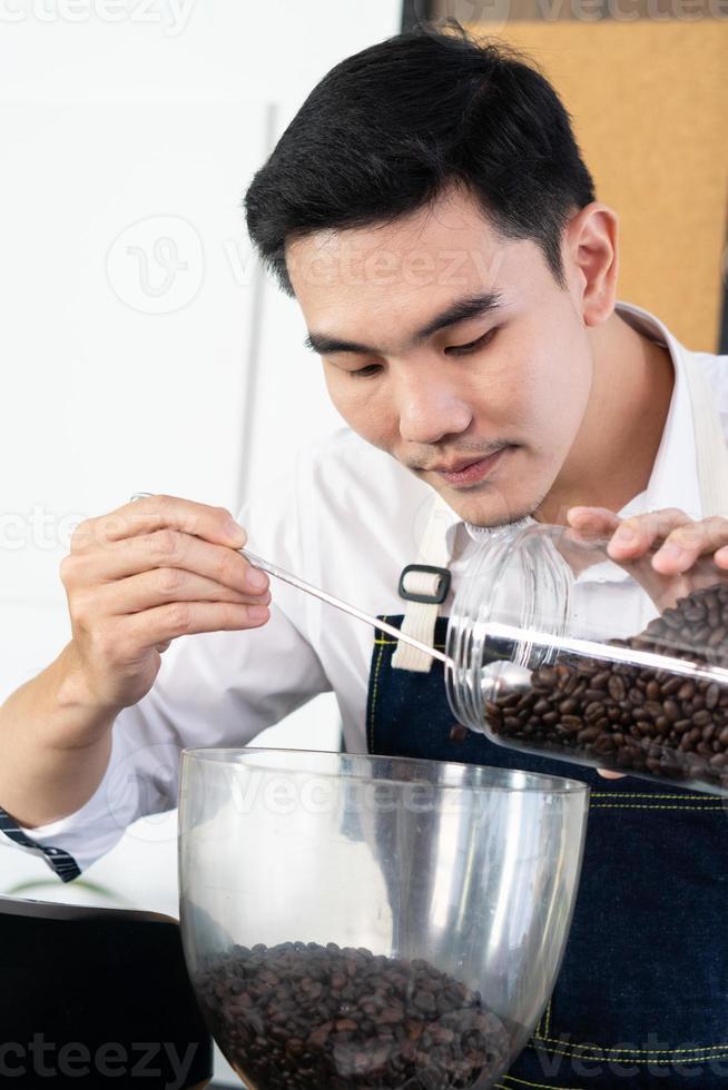jovem barista asiático coloca grãos de café em uma máquina de moer em um café foto