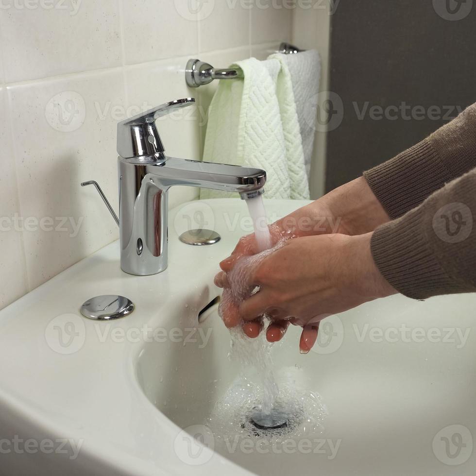 homem irreconhecível lavando as mãos foto
