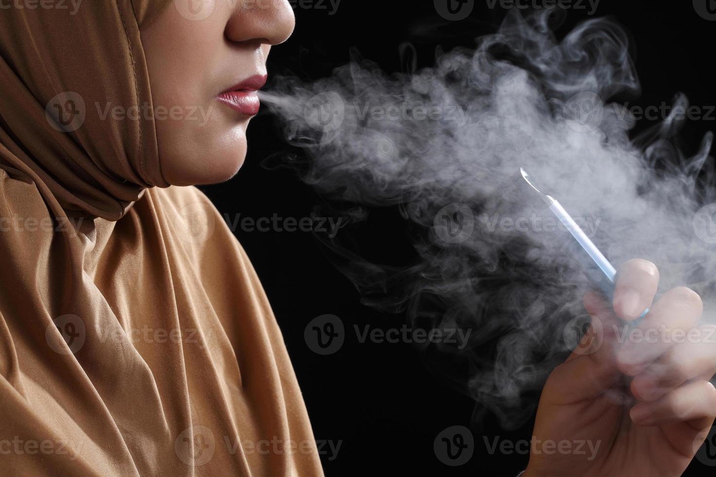 close-up jovem mulher muçulmana fumando cigarro em fundo preto foto