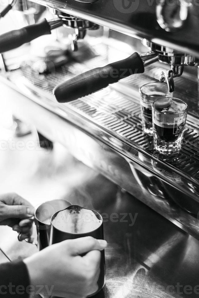 fazendo café expresso em preto e branco fechar detalhes com uma moderna cafeteira e óculos foto