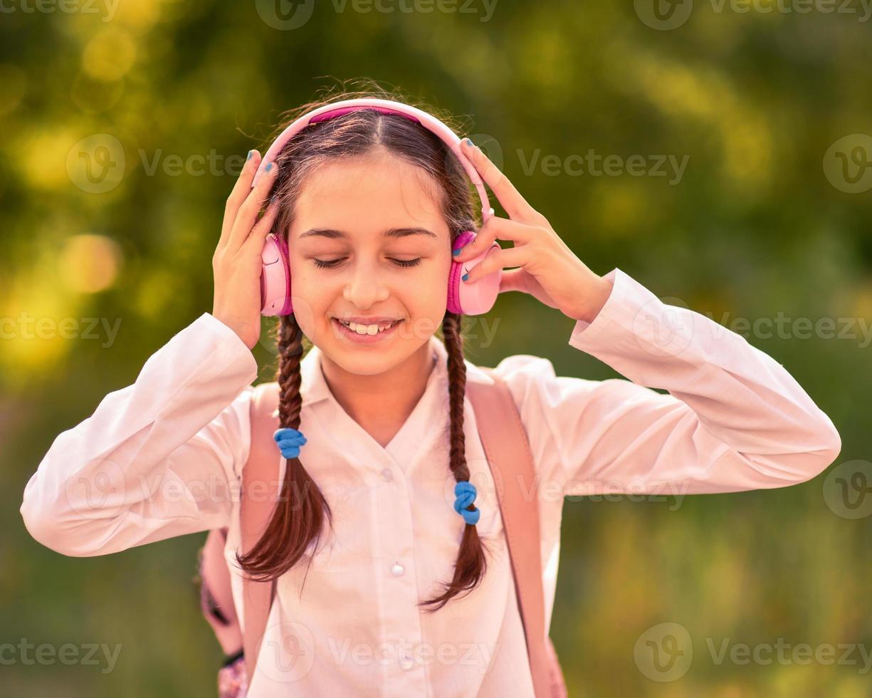 adolescente ao ar livre ouvindo música com fones de ouvido sem fio foto