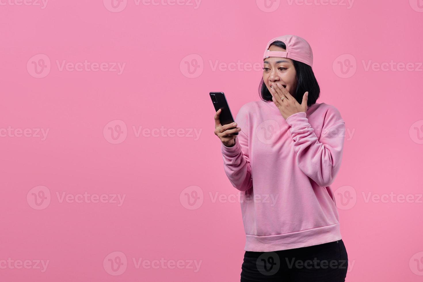jovem asiática chocada usando telefone celular foto