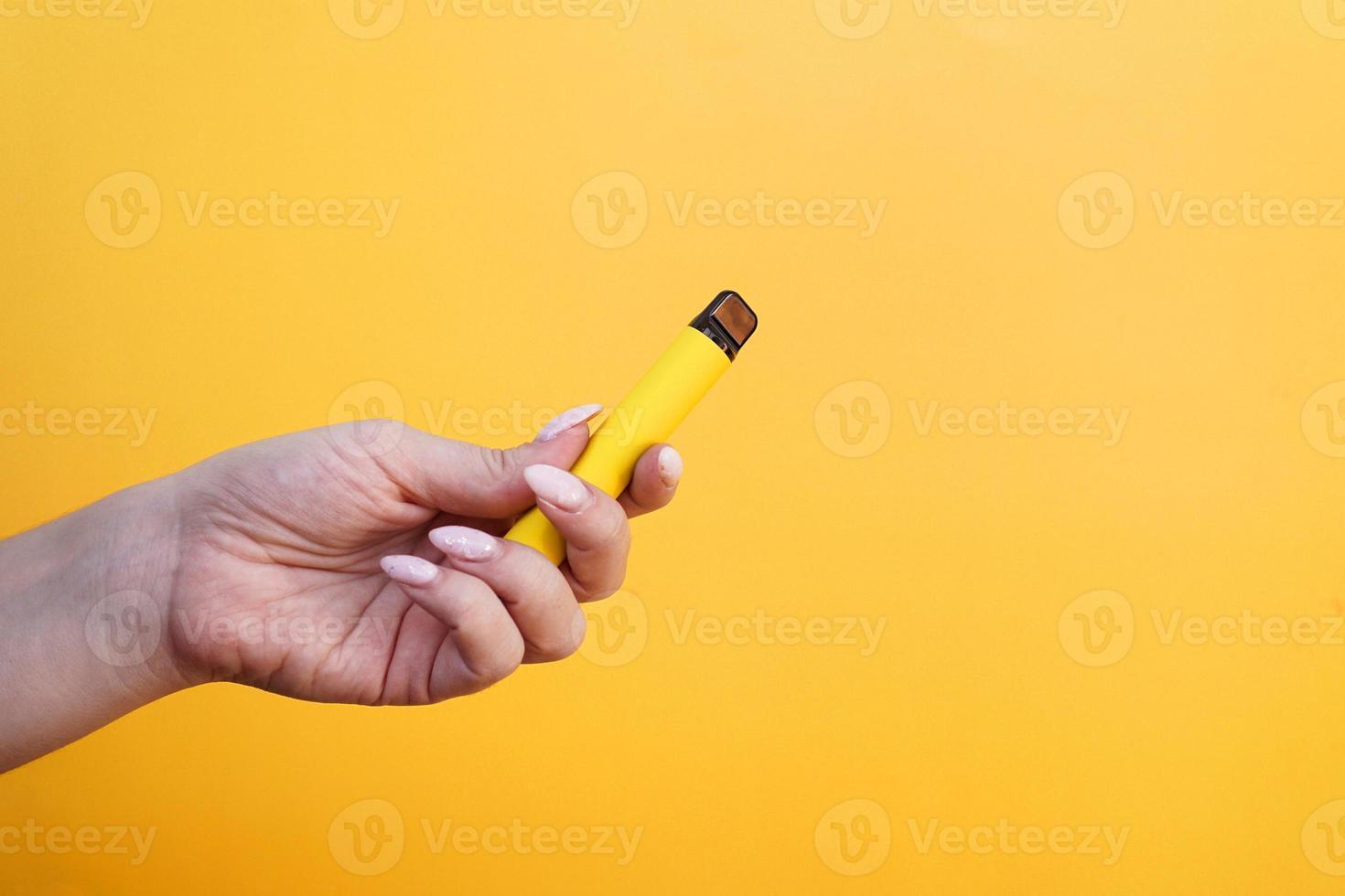 cigarro eletrônico descartável amarelo em mão feminina foto