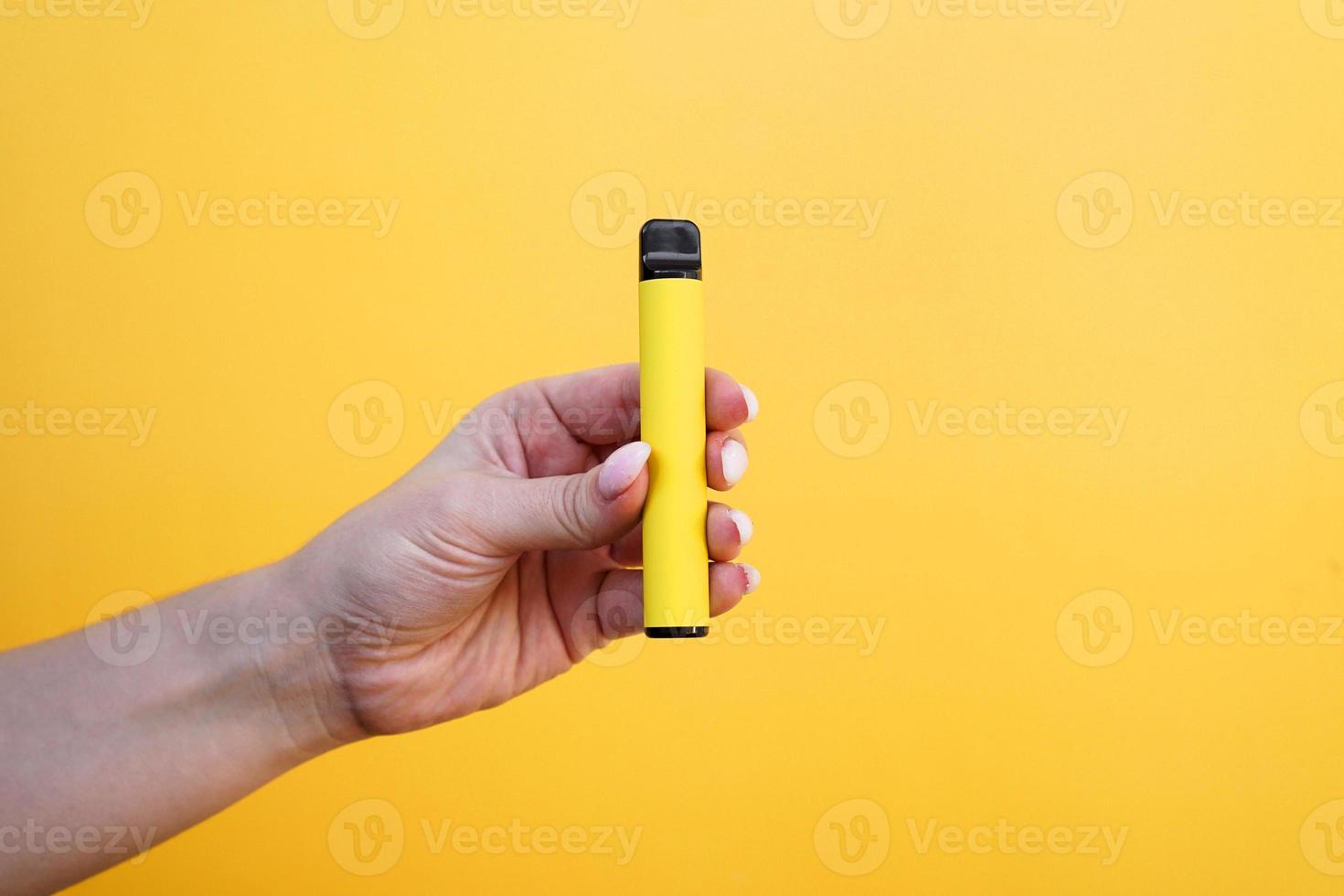 cigarro eletrônico descartável amarelo na mão feminina. foto