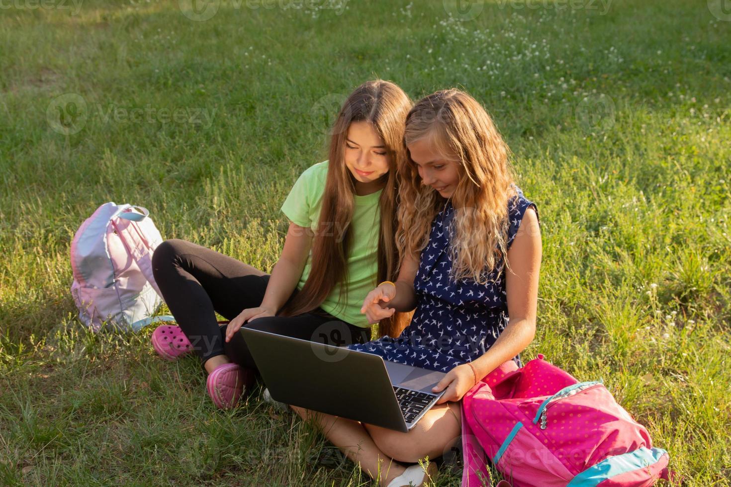 duas garotas com laptop na grama do lado de fora foto