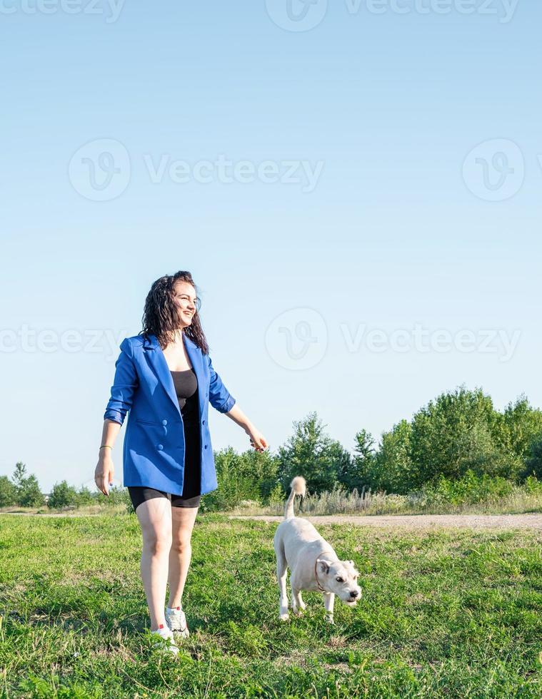 jovem mulher atraente passeando com o cachorro no parque em dia de verão foto