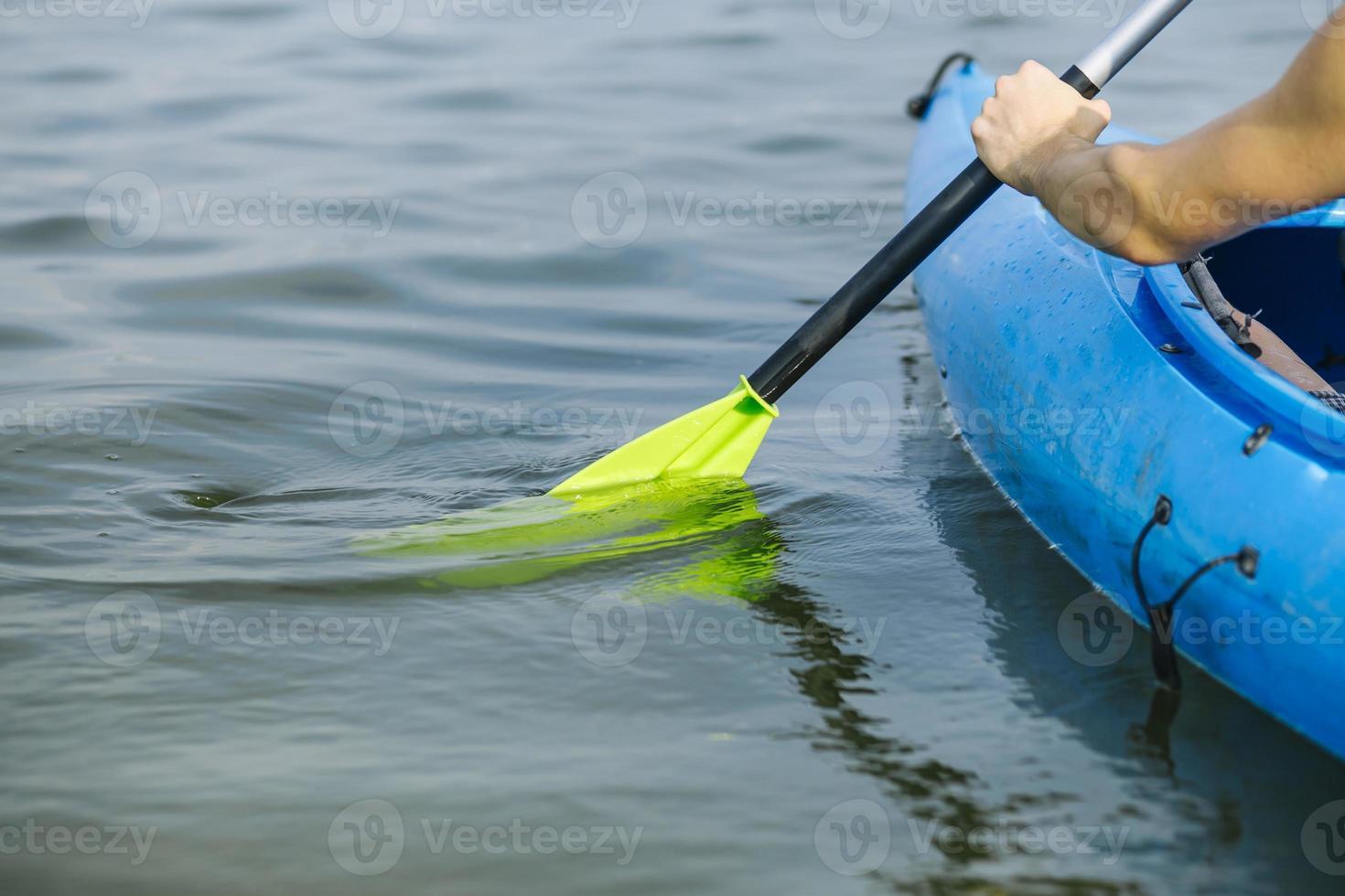 homem remando de caiaque no lago foto