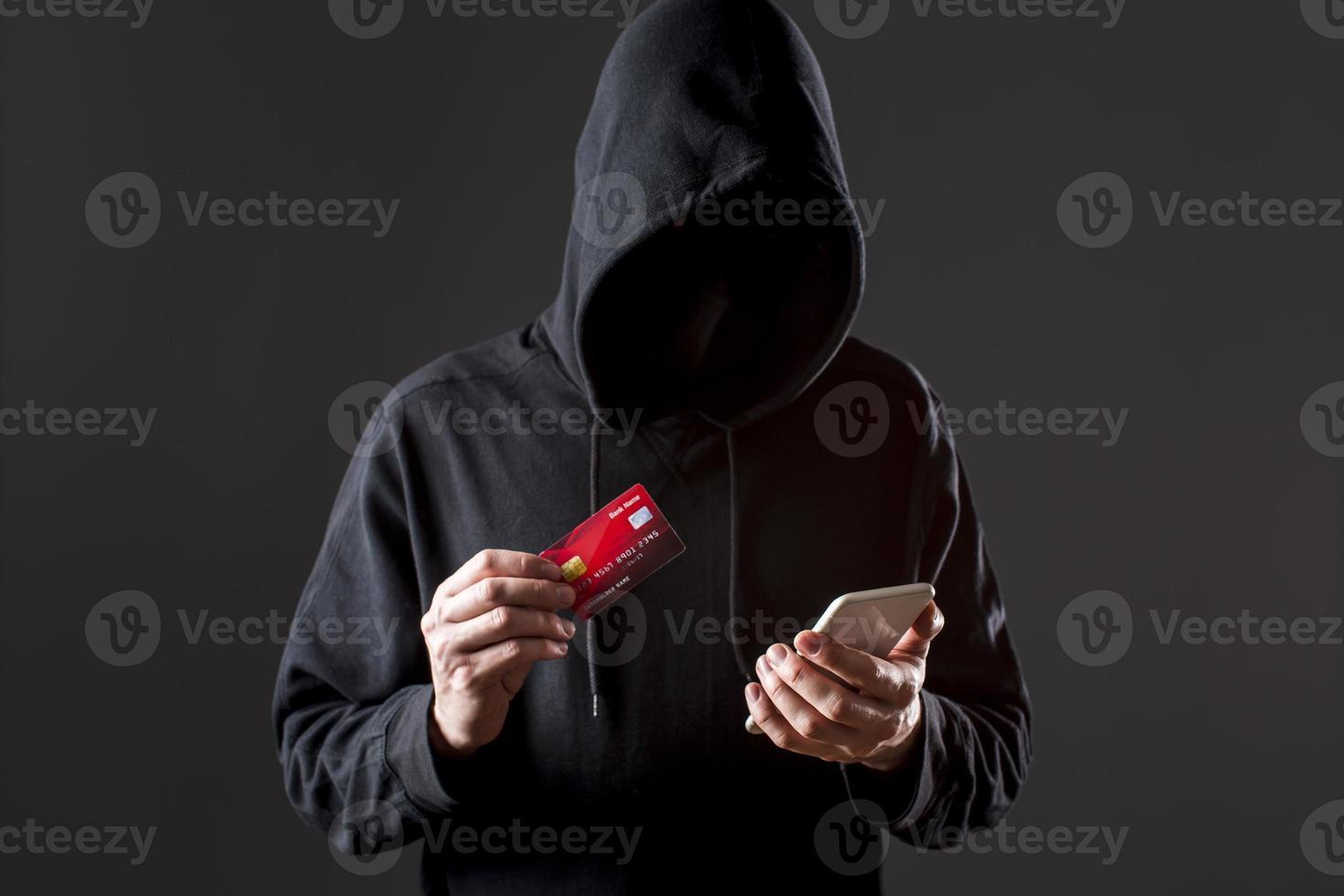 hacker masculino segurando smartphone e cartão de crédito foto