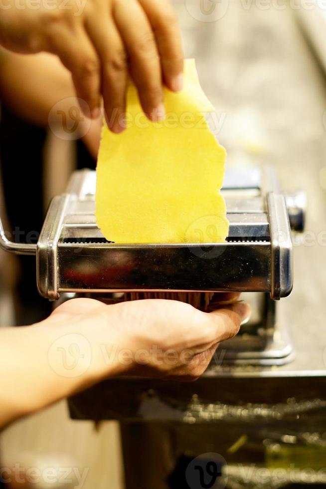 chef fazendo macarrão com máquina, macarrão caseiro fresco foto