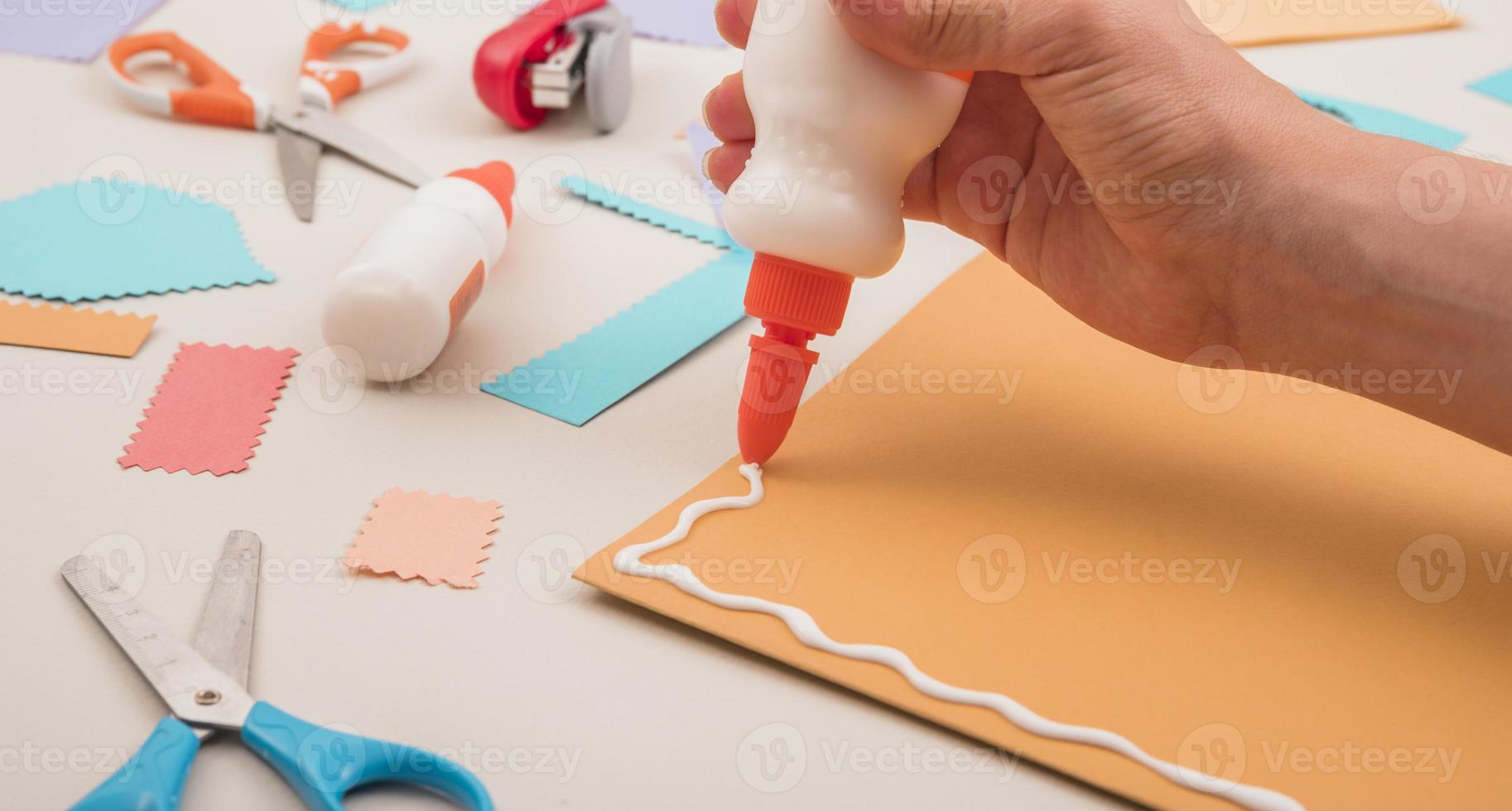 mão aplicando cola branca em papel laranja foto