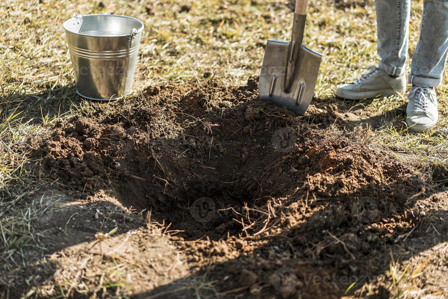 homem cavando um buraco com uma pá, plantando uma árvore foto
