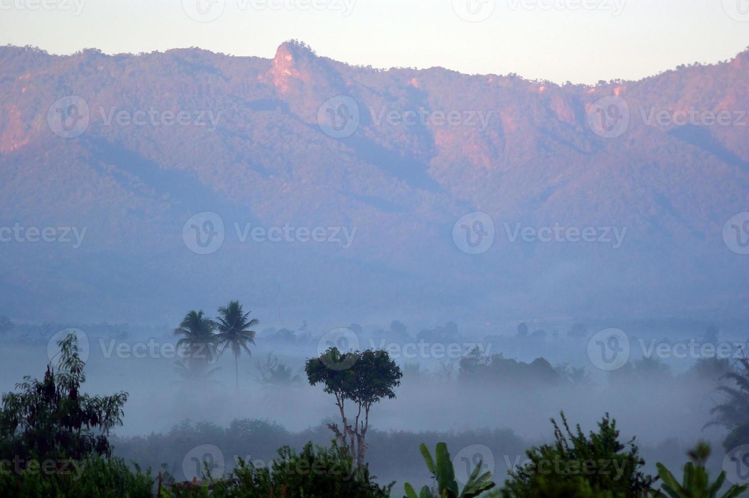 bela neblina matinal e vista para a montanha de fundo foto