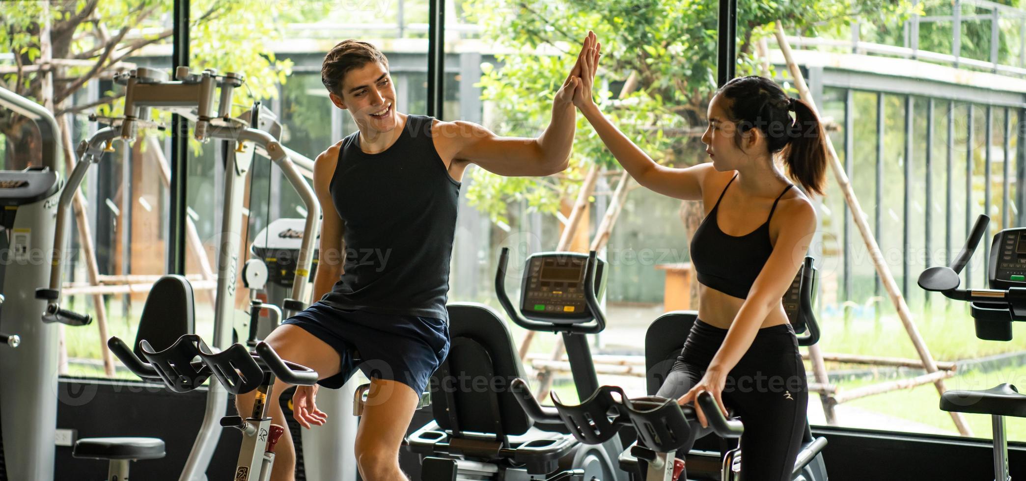 casais jovens se exercitam na academia para fortalecer o corpo foto