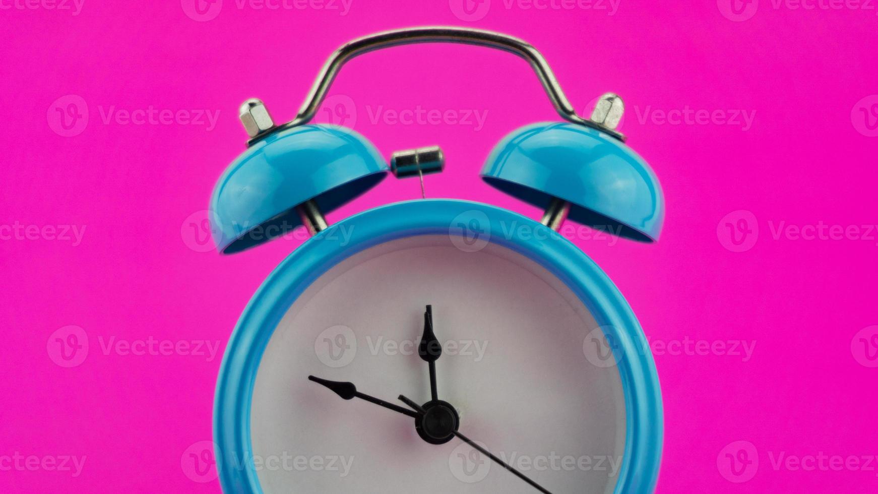 despertador azul em fundo rosa foto
