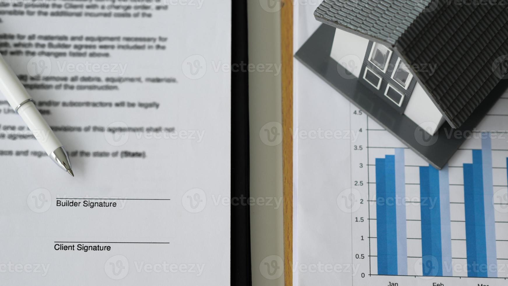 caneta colocada em documentos de contrato e casas modelo em gráficos de dados. foto