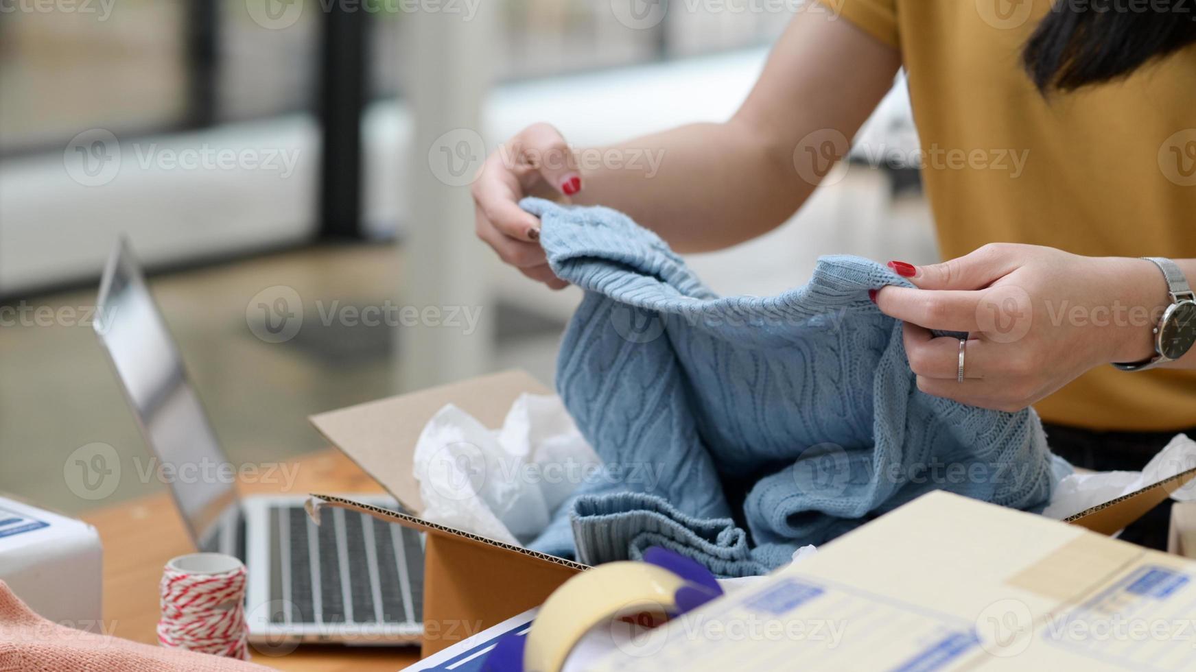 venda on-line mulher embalando camisolas em caixas para entrega. foto