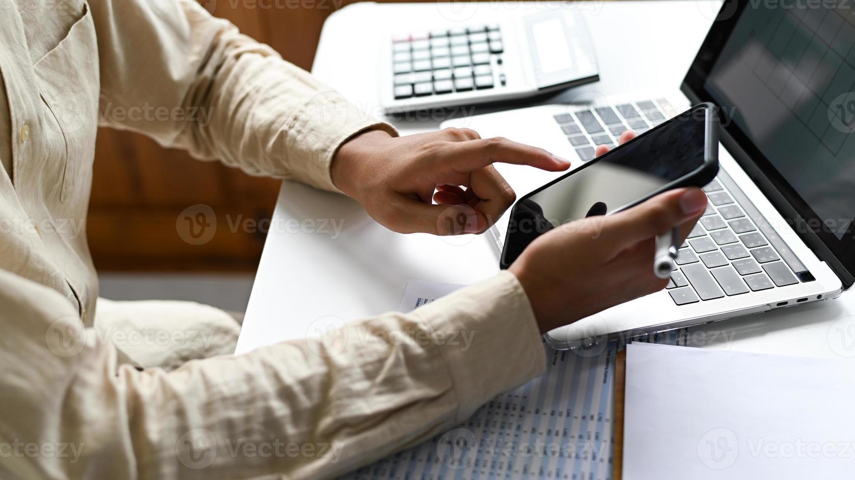 mão opera um smartphone com um laptop e gráficos. foto