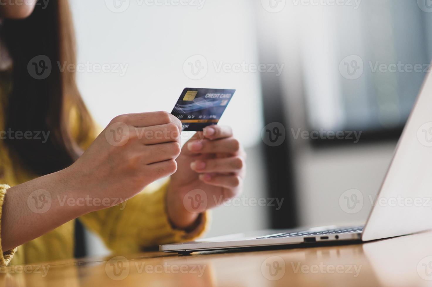 jovem segurando o cartão de crédito na mão e o laptop na mesa. foto