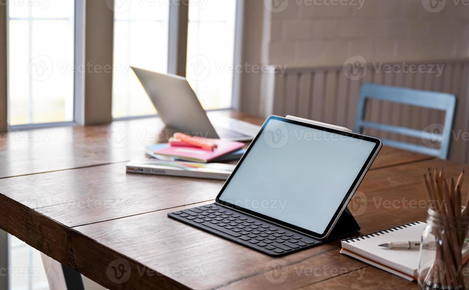 tela em branco do tablet e equipamento de escritório na mesa de madeira. foto