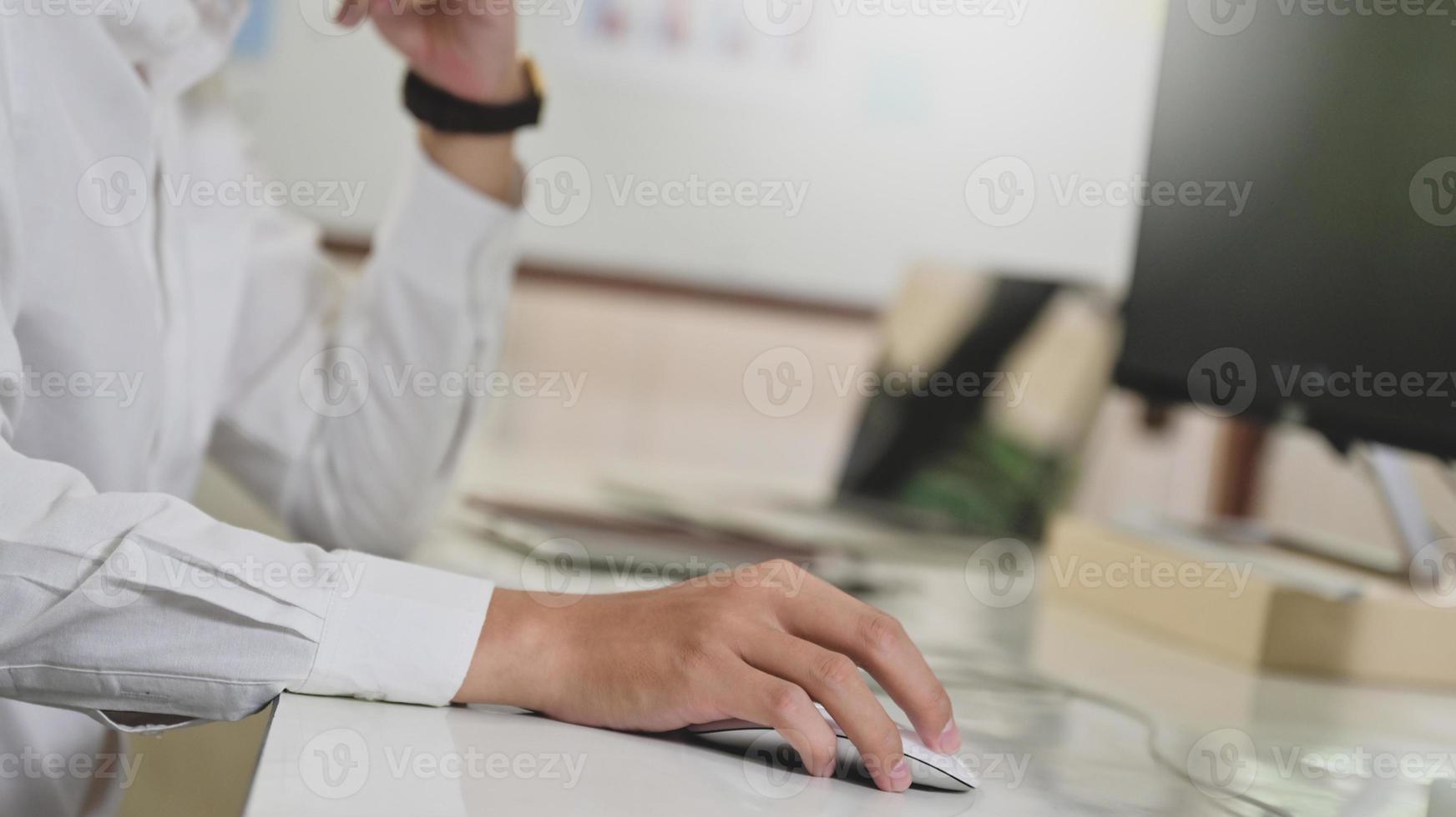 mão do programador usando o mouse do computador, computador na mesa do programador. foto