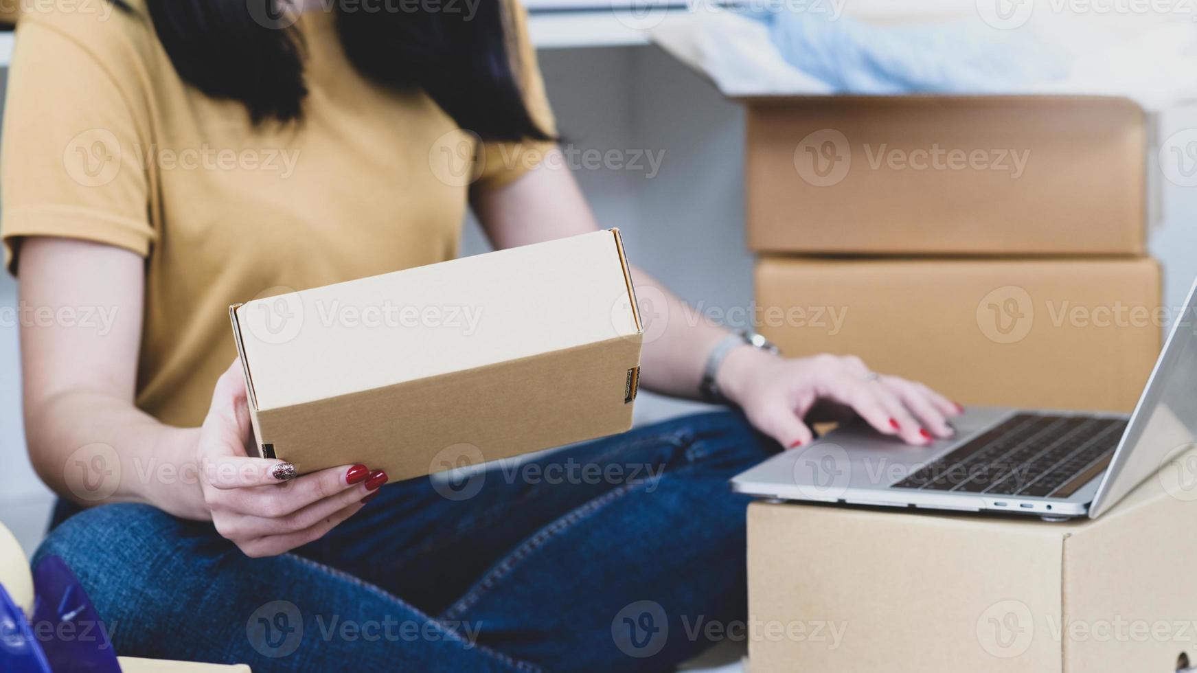 mulher segurando caixas de encomendas e usando o laptop, vendendo produtos online. foto