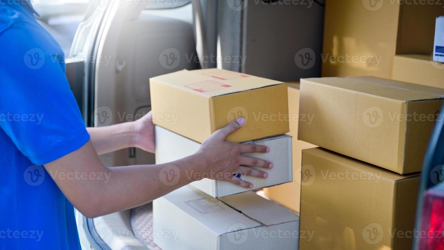 O mensageiro estava tirando a caixa de papel do porta-malas para entrega. foto