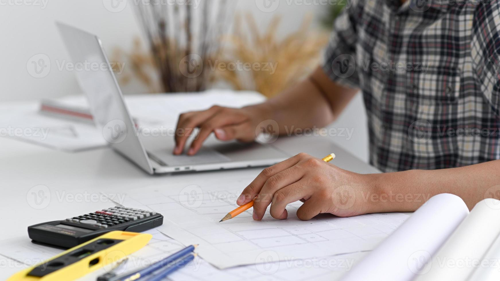 o homem usa um lápis para escrever na planta da casa. foto