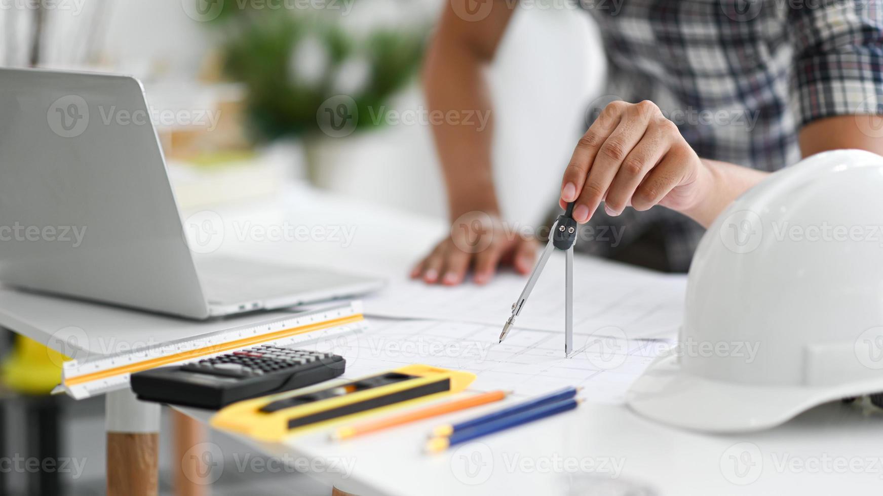 jovem arquiteto usando a rotatória para escrever sobre a planta da casa. foto