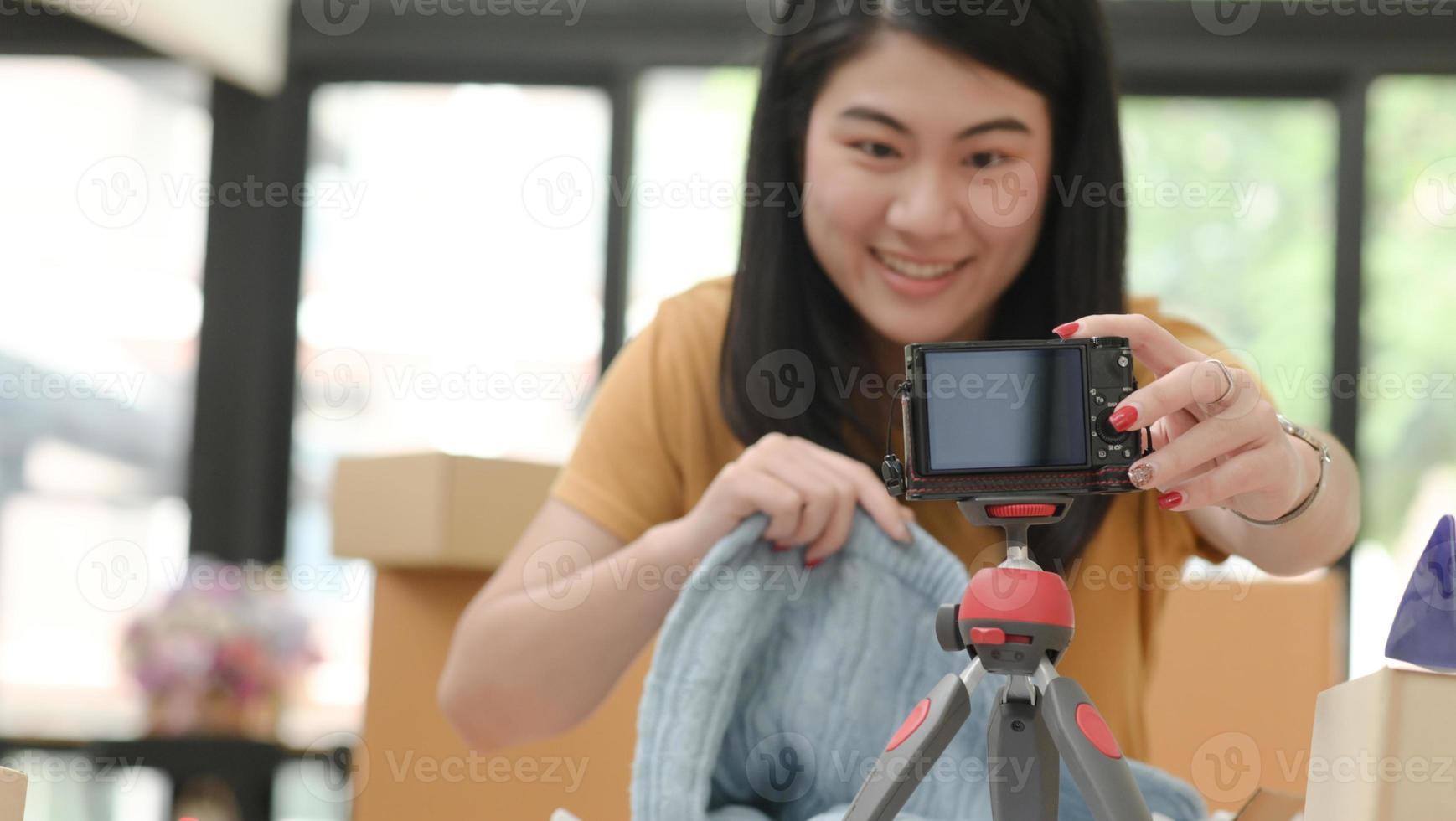 mulher sorridente liga uma câmera para vender online. foto